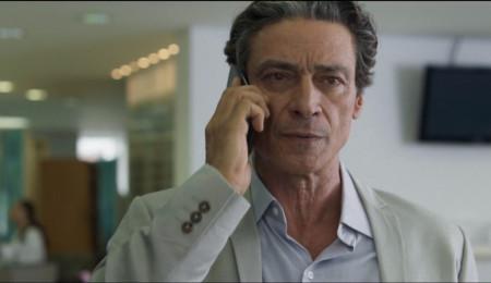 homem grisalho com celular na mão esquerda